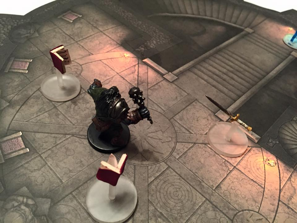 An orc deals with a flying sword and a pair of flying books inside the wizard's tower.