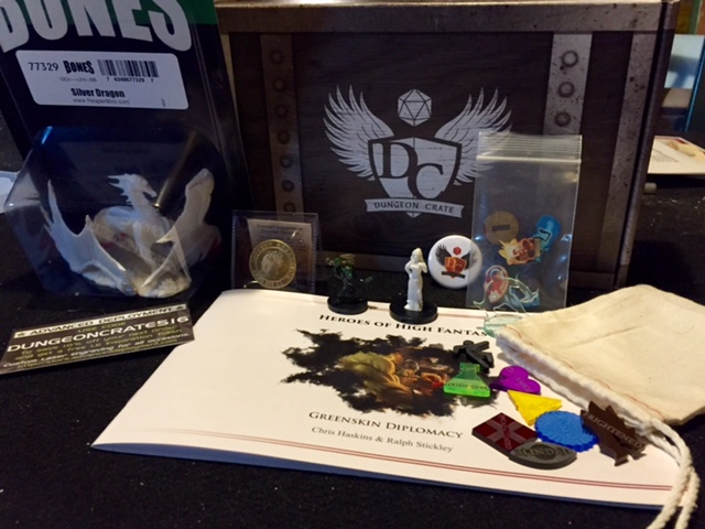 May's box from Dungeon Crate features two adventures, two sets of tokens, several miniatures and a coin.